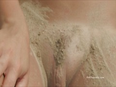Naked girl rubs sand a...